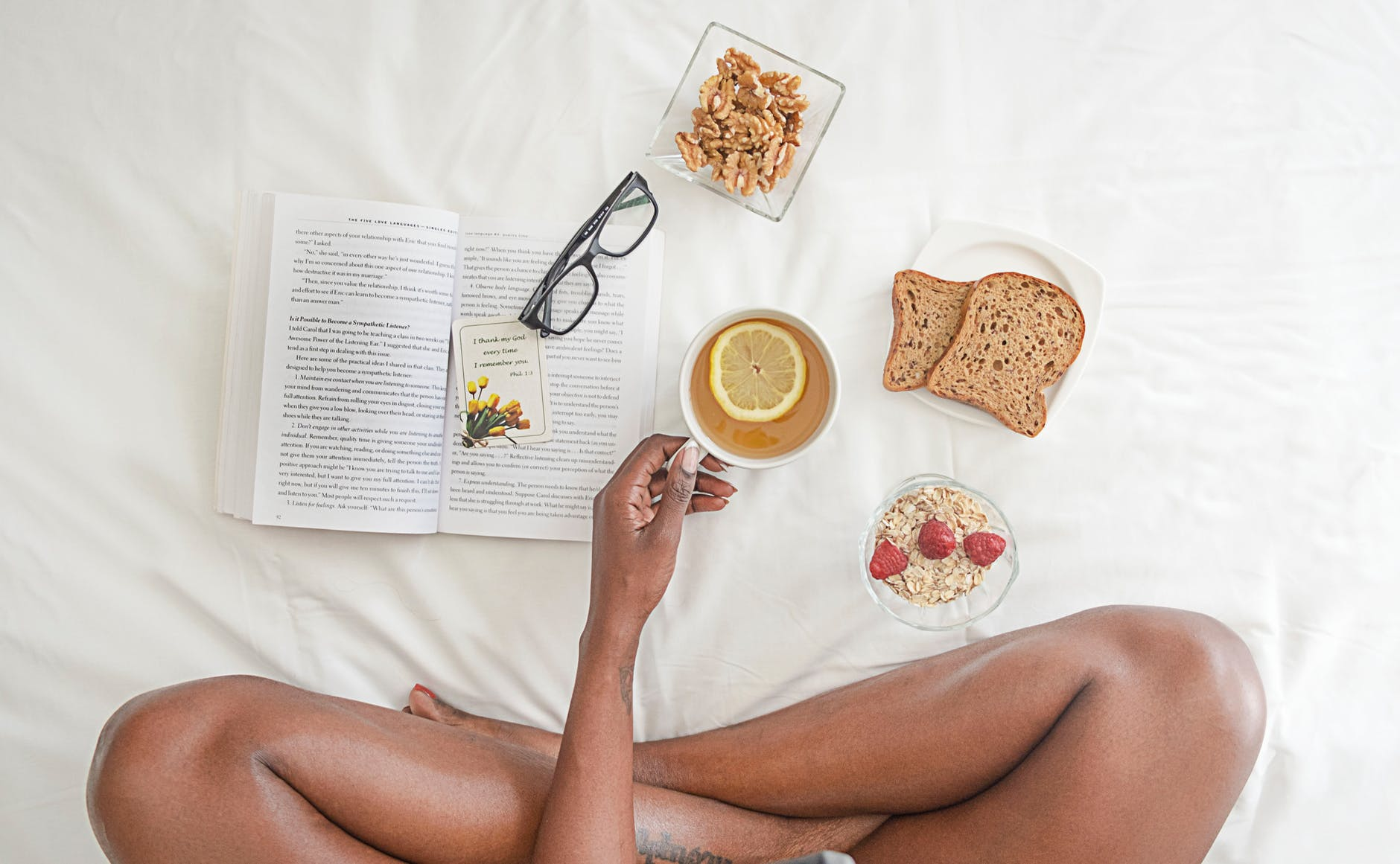 person holding white ceramic mug with lemon near book and sliced bread on white comforter